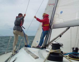 Skipper en pied de mât, discutant d'un nuage en approche.